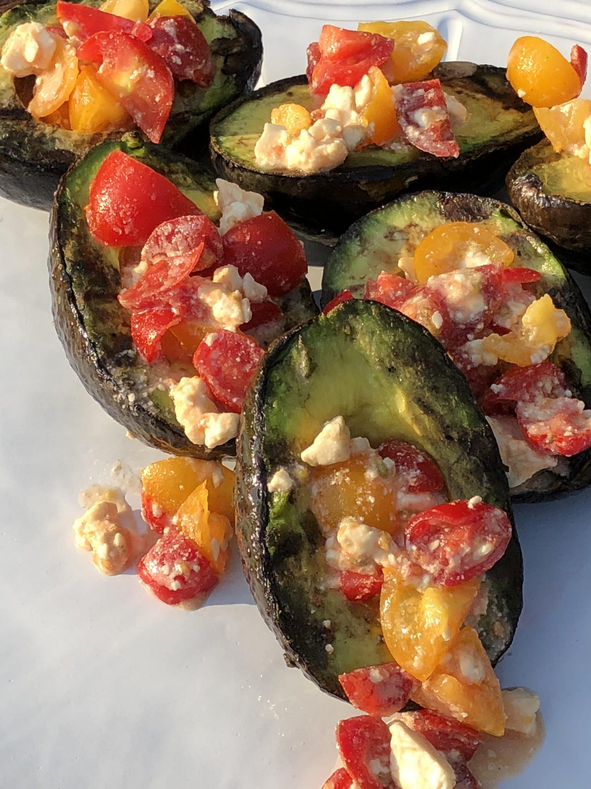 grilled avocado overflowing with tomatoes and feta