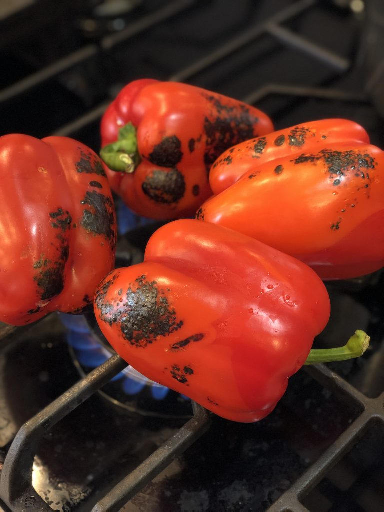 roasting the peppers over a gas flame