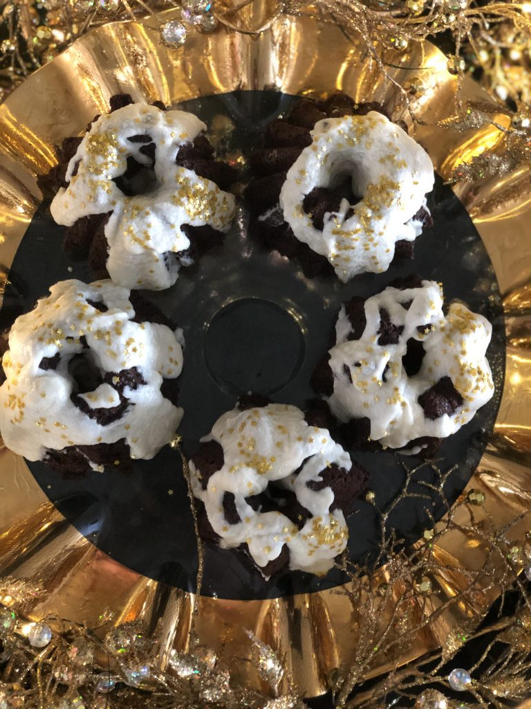 5 golden bundt cake rings with snowy whipped cream frosting